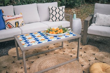 DIY tiled coffee table in outdoor patio with bowl of oranges on top