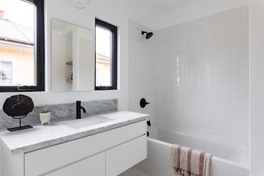 bathroom with shower/bathtub combo, bathroom vanity; grey, white and black color scheme