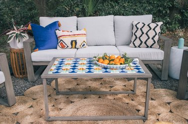 DIY tiled coffee table in outdoor patio with a bowl of oranges on top in front of sofa with colorful pillows