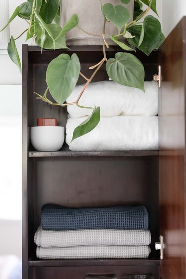 bathroom linen cabinet full of towels