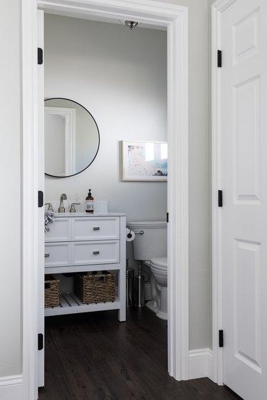 freestanding bathroom vanity and sink, toilet and circular mirror