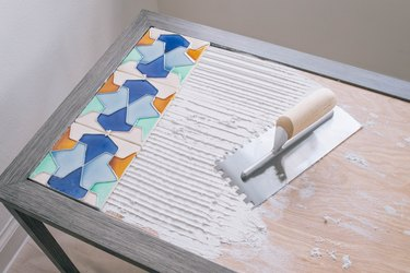 Tiles pressed into adhesive which has been scraped with a notched trowel