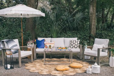 DIY tiled coffee table in in outdoor patio with colorful pillows, fringe umbrella and round woven rug