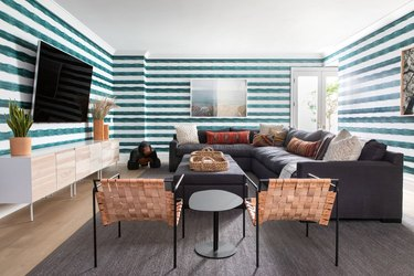 striped teal color wallpaper in living room with sectional sofa