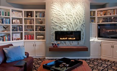 basement fireplace with plexiglass mantel, built-in shelves, and leather couch