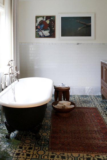 traditional bathroom idea with black clawfoot tube, cement tile, red rug