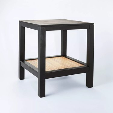 black accent table with woven rattan shelf
