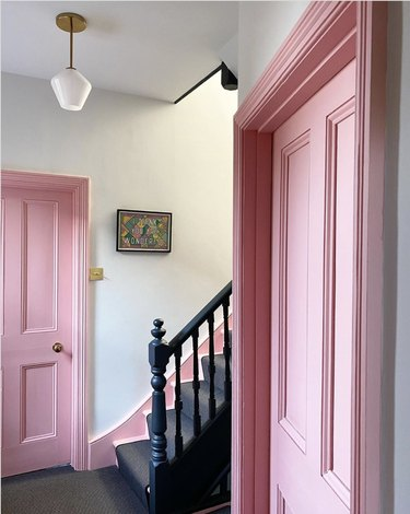 Gray striped stair runners next to pink doors