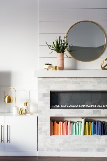 basement fireplace below white brick mantel with gold circle mirror and decorative plant