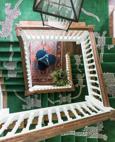 green and leopard-print stair runners on spiral staircase with wood railings