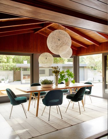 teal color chairs in midcentury modern dining room with wood ceiling