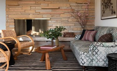 stone basement fireplace with wood bench and woven accent chairs