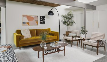 living room space with burnt orange couch and two chairs