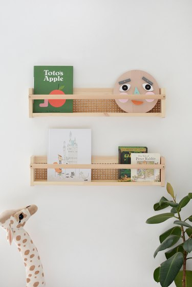 Cane shelf with childrens books and toy giraffe and plants