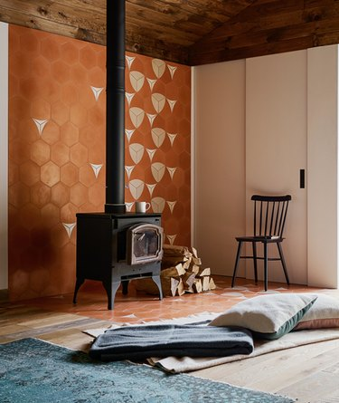 wood-burning basement fireplace in front of floor pillow and orange accent wall