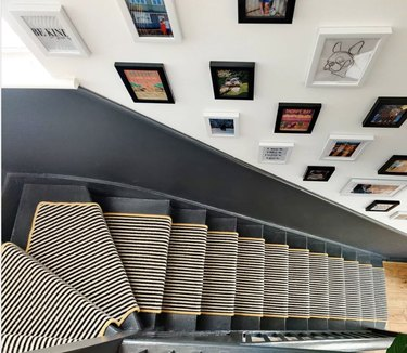 Small-striped stair runners on gray stairs with gallery wall
