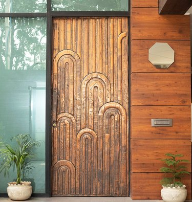 Art deco door with curved patterns in a bronze material
