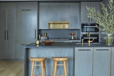Gray quartz countertop colors, with kitchen island, wood barstools, vase with branches.