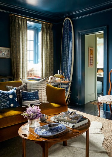 blue traditional living room with mustard velvet sofa and layered rugs