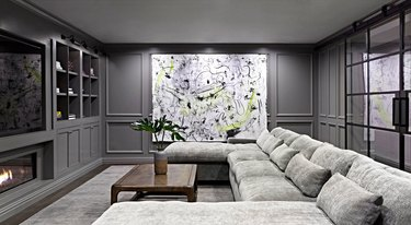basement wall ideas with abstract art piece in gray basement with a sectional couch