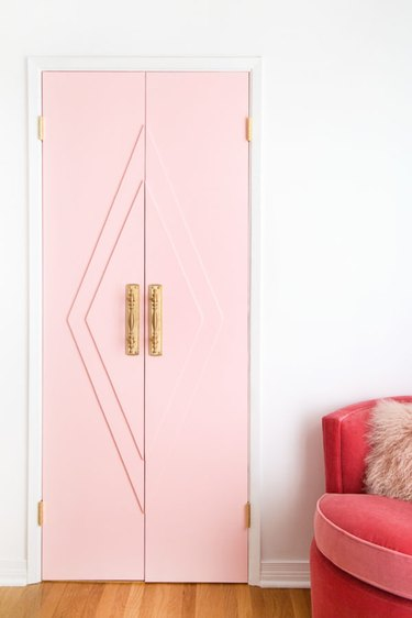 Art deco door in pink with geometric accents and brass handles