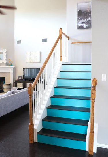 turquoise ombre painted stairs with white railing and wood banister