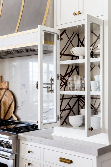 Traditional kitchen design with white cabinets and black and white wallpaper inside cabinet