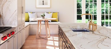 Gold-veined quartz countertop colors, light wood floors, brass faucet, breakfast nook, round wood dining table, yellow and white cushions.
