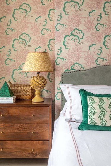 traditional bedroom color schemes with pink and green wallpaper and wood nightstand