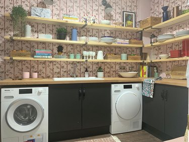 basement laundry room ideas with washer and dryer and patterned wallpaper.