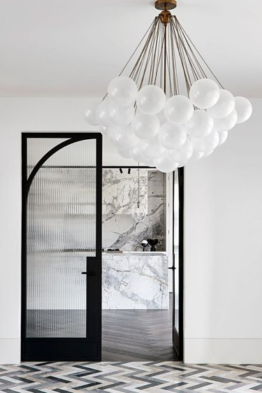 Art deco door with black linear detailing and bubble chandelier