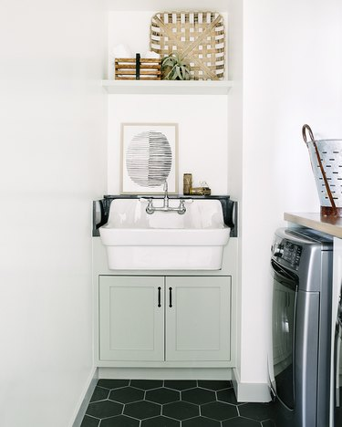 basement laundry room ideas with black hexagon tile floor and white sink.