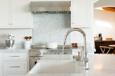 kitchen with white cabinets and white marble countertops and a running sink