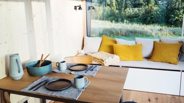modern tiny house dining area with table and window bench