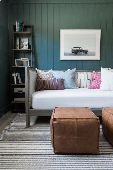 green basement paint colors in basement with leather, shiplap, and colorful throw pillows