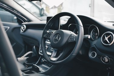 all black mercedes car interior showing steering wheel and driver's seat