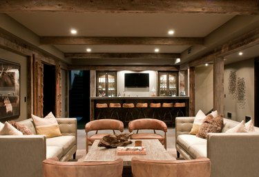 rustic basement ideas with beams and leather chairs