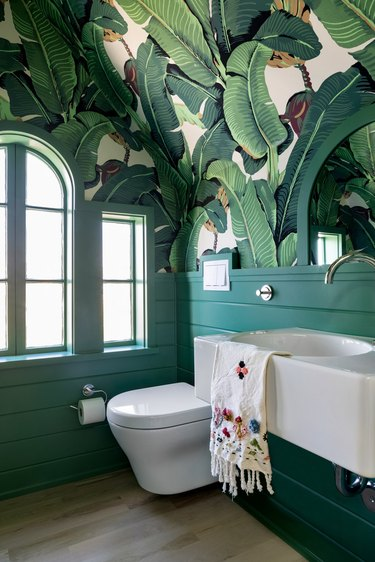 attic bathroom ideass with banana leaf wallpaper and green board and batten