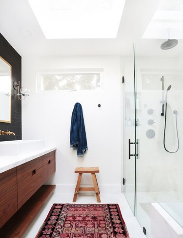 bathroom curtain idea in mostly white bathroom with a wood vanity, black wall behind the mirror, small window and skylight