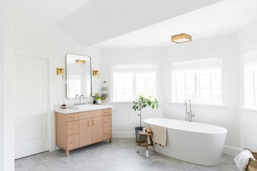 bathroom curtain idea in large bright space with a soaking tub, a wood vanity, and lots of windows