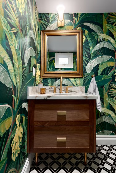 Jungle-themed wallpaper in maximalist bathroom with floating sink vanity