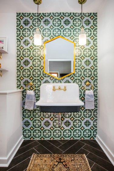 green tile wall in maximalist bathroom with chevron floor and floatink sink basin