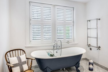 bathroom curtain idea with navy blue clawfoot tub in a white bathroom with white plantation shutters on the window
