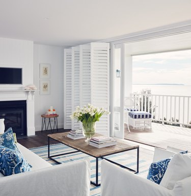 window treatments for sliding glass doors in white coastal living room with white shutters