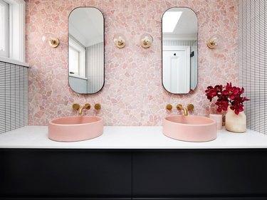 Millennial pink bathroom sink idea with pink backsplash and black vanity cabinet