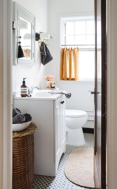 Modern bathroom storage with a medicine cabinet and hamper by Erin Francois of Francois et Moi