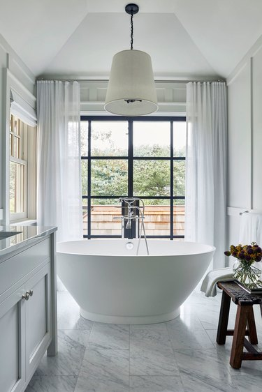 bathroom curtain idea with soaker tub in the middle of a large bathroom with marble tiles and a floor-to-ceiling window