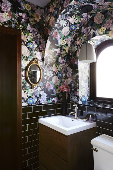 Black floral wallpaper in maximalist bathroom with wood vanity and arched window