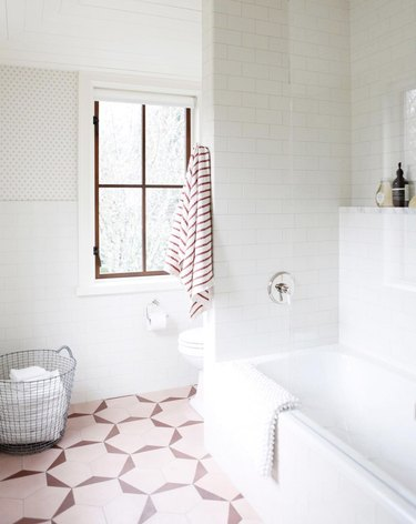 bathroom curtain idea in mostly white bathroom with pink floor tiles and a vinyl roller shade on the window