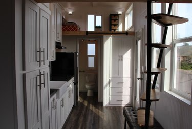 metal tiny house stairs in room with dark wood floors, wood, and white cabinets.